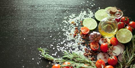 Vegetables, spices, olive oil, coarse sea salt against a dark background