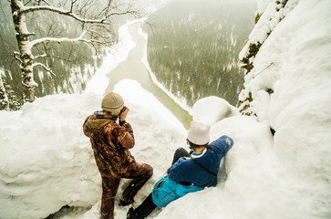 Caucasian hikers enjoying view from snowy hilltop