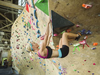 Caucasian woman climbing indoor rock wall