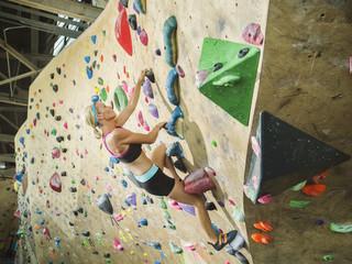 Caucasian woman climbing indoor rock wall
