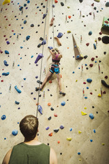 Caucasian man belaying climber at indoor rock wall