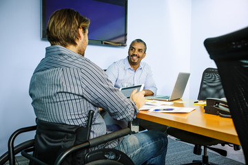 Businessmen talking at conference table in office