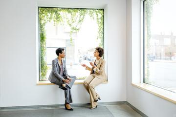 Businesswomen talking in window of office lobby