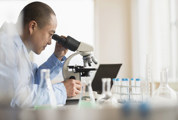 Korean scientist using microscope in laboratory