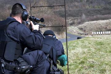 Military sniper aims at a target