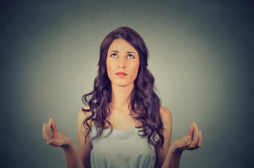 young woman meditating looking up isolated on gray wall background
