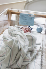 Mixed race wrapped in blanket in hospital crib