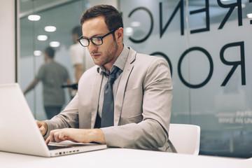 Caucasian businessman working on laptop in office