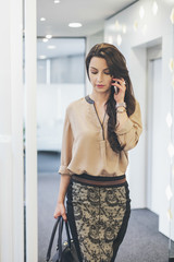 Caucasian businesswoman talking on cell phone in office corridor