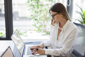 Caucasian businesswoman working at laptop at desk