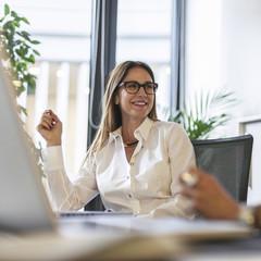 Caucasian businesswoman smiling at desk in office
