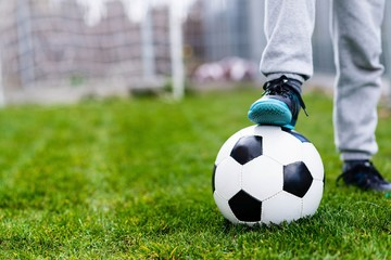 Feet of child on football / soccer ball on grass