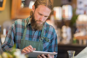 Caucasian server using digital tablet in cafe