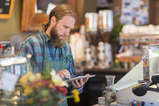 Caucasian server using digital tablet in cafe