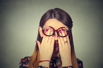 Closeup portrait young woman in glasses covering face eyes using her both hands