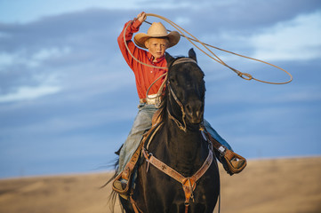 Caucasian boy on horse throwing lasso