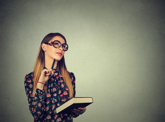 woman with book thinking dreaming has many ideas looking up