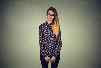 Sad shy insecure young woman in glasses looking down avoiding eye contact