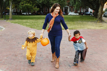 Mother and sons trick or treating together on Halloween