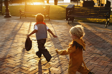 Boys playing in costumes on sidewalk