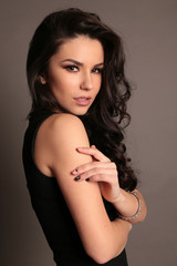 gorgeous woman with dark hair and evening makeup in elegant dress