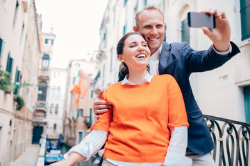 Happy smiling couple take a selfie photo on the old Venice stree