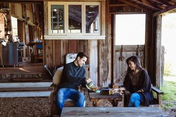 Couple drinking tea in barn