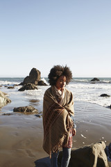Mixed race woman wrapped in blanket on beach