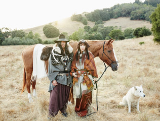 Nomadic couple with horse and wolf standing in field