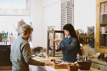 Mixed race business owner serving customer in clothing store