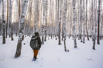 Mixed race man walking in snowy forest