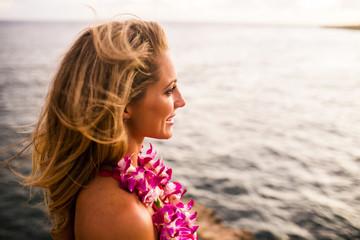Caucasian woman wearing flower lei by ocean