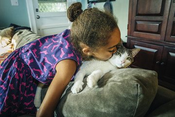 Mixed race girl kissing pet cat on sofa