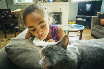 Mixed race girl playing with pet cat on sofa