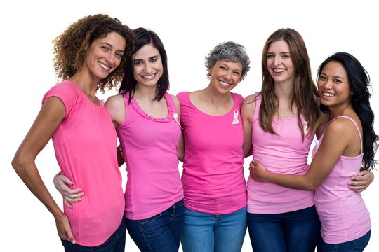 Smiling women in pink outfits posing for breast cancer awareness