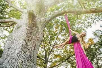 Acrobatic Caucasian girl hanging on fabric under tree