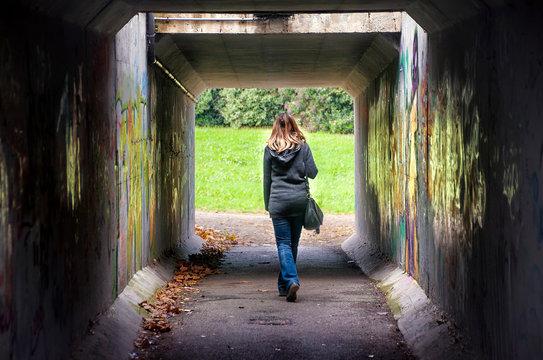 woman walk alone tunnel dark underpass