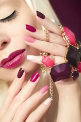 Разноцветный бордовый маникюр крупным планом на ногтях и макияж на девушке.