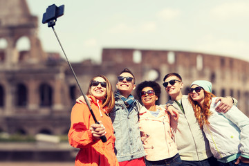 happy friends with smartphone selfie stick