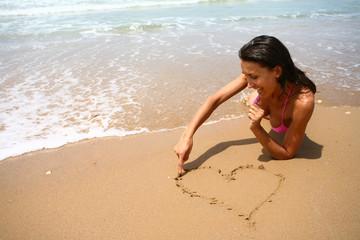 femme à la plage qui dessine un coeur dans le sable