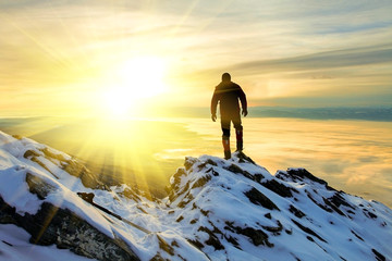 The man to stand on mountain top at sunrise