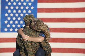 Returning Caucasian soldier hugging wife
