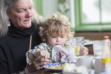 Caucasian grandmother and grandson eating dinner in restaurant
