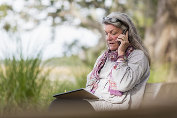 Older Caucasian woman talking on cell phone outdoors