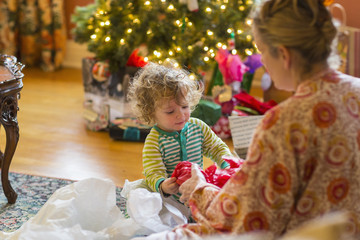 Caucasian mother and baby son opening presents near Christmas tree