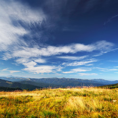 clouds over mountains and yellow grass