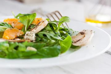 Sommer salad with rocket salad, mandarin, mushrooms and cheese gorgonzola in a white ceramic bowl , closeup.