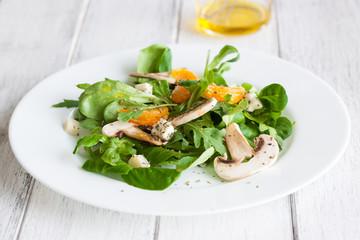 Sommer salad with rocket salad, mandarin, mushrooms and cheese gorgonzola in a white ceramic bowl , closeup..