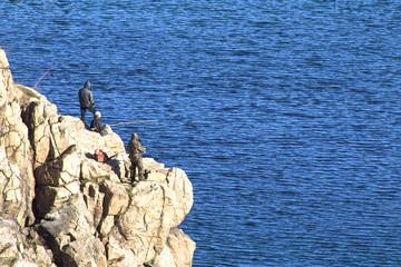 Fishermen catch fish on a rock. Horizontal shot, topic - fishing, hobbies, leisure.