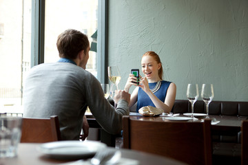 Young couple in restaurant, woman using cell phone